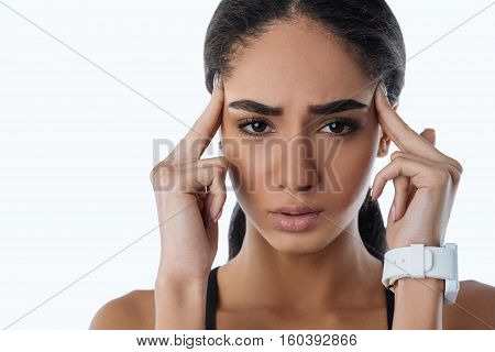 Have a headache. Sad female touching her temple with fingers looking straight at camera wearing smart watches, isolated on white background