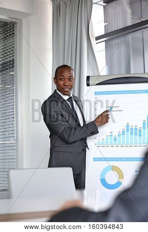 Young businessman explaining graph while giving presentation in board room