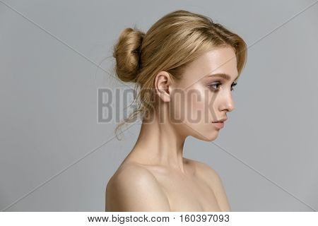 beautiful model lady with natural make-up and blonde hair studio fashion shot on gray background perfect skin