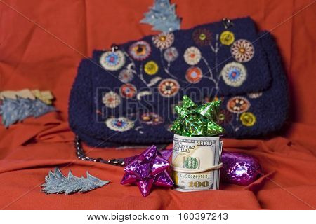 Bundle of US dollars in focus and colorful bows with a handbag in the blurred background.
