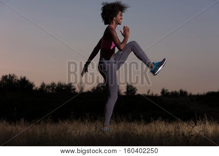 Young healthy black woman is doing stretching exercise relaxing and warm up after jogging and running in the nature beautiful summer evening