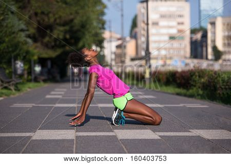 portrait of a young beautiful African American girl doing stretching after running beautiful summer morning on the streets of the city