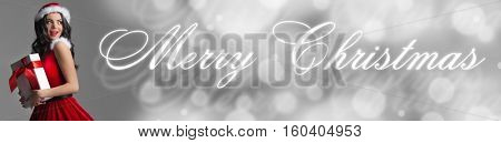 Excited surprised woman in red santa claus outfit holding Christmas present and Merry Christmas text on gray background