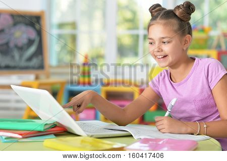 Little girl doing her homework at home and using a laptop