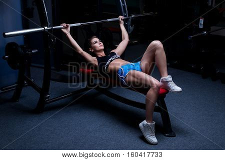 Sexy sporty woman doing power fitness exercise at sport gym. Beautiful girl working out in gym