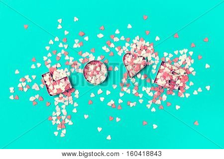 Love concept with letters LOVE and sweethearts on a pastel toning background. Top view with copy space