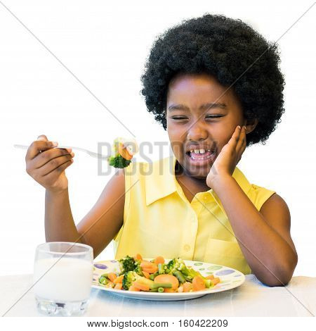 Close up portrait of little black girl refusing vegetable meal at dinner table.Isolated on white background.