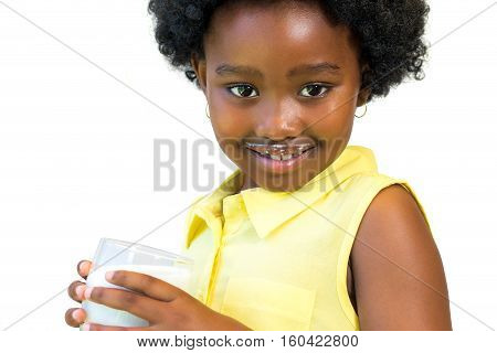 Close up portrait of little african girl drinking milk. Kid with afro hairstyle showing white mustache. Isolated on white background.