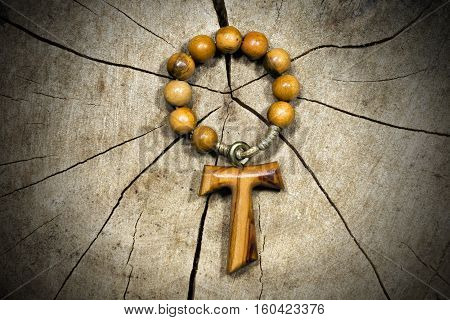 Tau wooden cross in shape of the letter t (religious symbol of St. Francis of Assisi) with rosary bead. On a tree trunk section