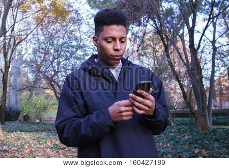 Black man sending messages with his smartphone in the field.