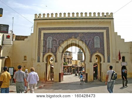 FEZ MOROCCO - MAY 19 2006: Tourists and pedestrians at the Bab Bou Jeloud (Blue Gate) the main entrance into the old medina Fes el Bali in Fez Morocco. The Moorish-style gate was built in 1913.