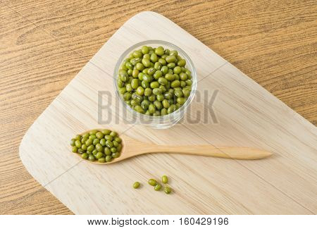 Cuisine and Food Top View Raw and Uncooked Mung Dried Beans in Wooden Spoon and Tumbler on Wooden Cutting Board.