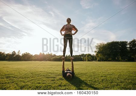 Couple Practicing Acrobatic Yoga In Park