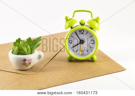 Green alarm clock and envelope on white background