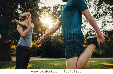 Young Couple Warming Up For Morning Workout In The Park