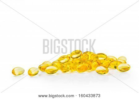clear golden yellow capsules on white background with copy space