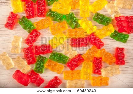 heap of assorted gelatin sweets. red green orange yellow gummy bear on wooden background