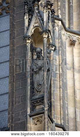 Priest sculpture in wall pinnacle of famous St. Vitus cathedral in Prague Czech Republic.