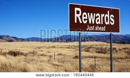 Rewards brown road sign with blue sky and wilderness