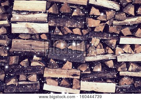 Dry Firewood neatly stacked in the woodpile. Background with a painted snow.