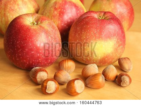 Fresh hazelnuts and red apples. Autumn food
