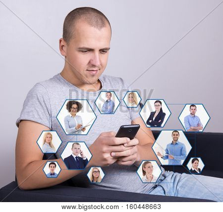 social media and internet addiction concept - handsome man sitting on sofa and using smart phone