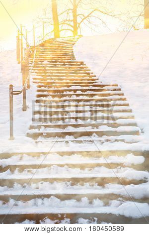 wintry hill with wooden staircase steps with snow covered into the light. shiny hopeful scenery sympathy design
