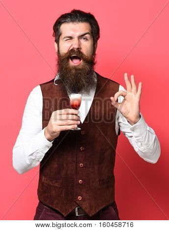 handsome bearded man with long beard and mustache on funny face holding glass of alcoholic shot in vintage suede leather waistcoat on red studio background