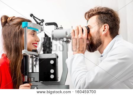 Eye doctor checking vision of young female patient with ophthalmologic device in the cabinet