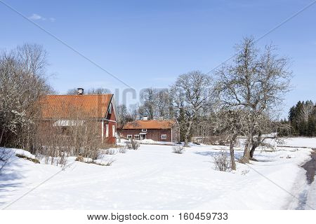 UPLAND, SWEDEN ON APRIL 10. View of a garden and some red wooden buildings on the countryside on April 10, 2013 in Upland, Sweden. Sunny day in spring, snow. Editorial use.