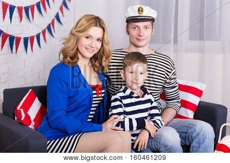 Happy Parents And Little Son In Sailors Uniform Sitting In Decorated Living Room