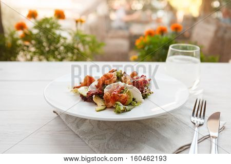 Restaurant food. Traditional italian seafood salad with shrimps and mozzarella on white round plate. Diet and healthy meals, candid image of served table