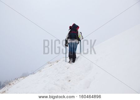 man trekking in foggy winter landscape going to the top