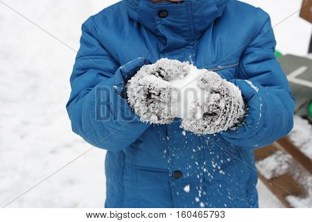 Children's winter games outdoors. The image of a child making snow snow lumps.