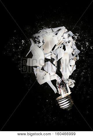Smashed or exploded incandescent light bulb on black