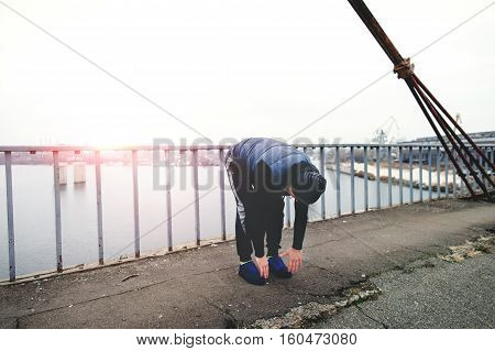 Fitness man doing workout on a city bridge on the sunset