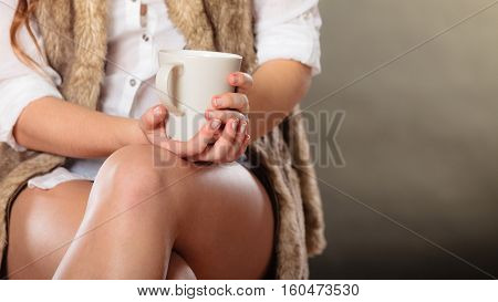 Young girl holding tea cup in hands. Woman having a break.