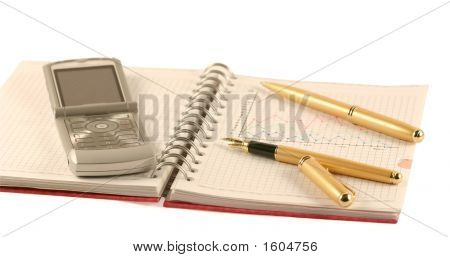 Two Pens On The Open Writing-Book And  Mobile Phone