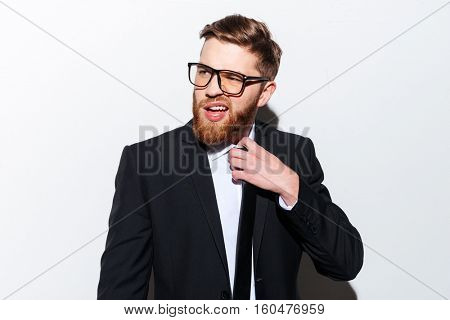 Young bearded business man in glasses and suit corrects tie with open mouth and looking aside. Isolated gray background
