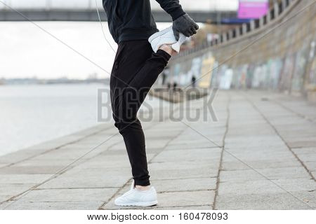 Closeup of man athlete standing and stretching legs outdoors