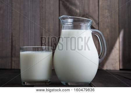 full jug and glass with milk on wooden background