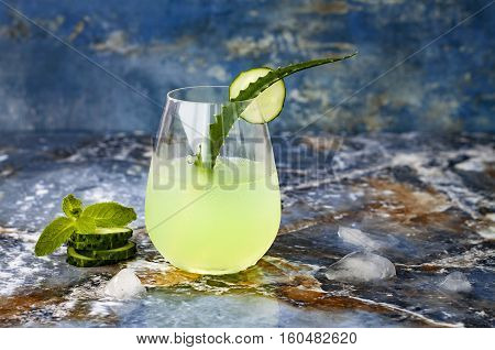 Sparkling cucumber mint gin and tonic fizz with aloe vera on marble table. Copy space. Dragon tail cocktail for fans party