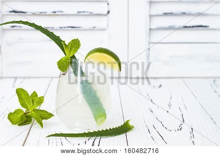 Sparkling cucumber mint gin and tonic fizz with aloe vera on white rustic table. Copy space. Dragon tail cocktail for fans party