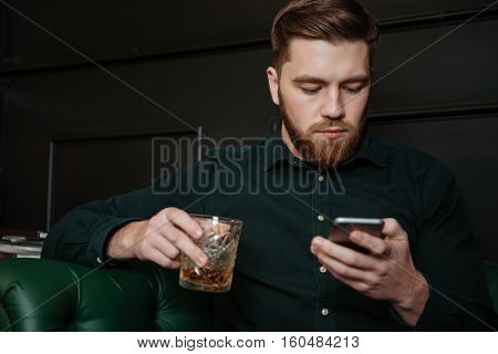 Serious man sitting in an armchair and drinking whiskey holding cellphone and looking on it.