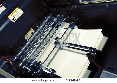 Printing offset machine with a stack of paper.