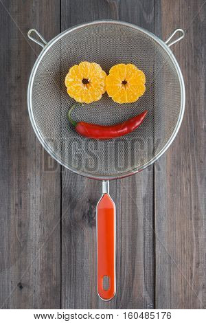 smile made with peeled mandarine tangerine as eyes, pepper chili as mouth in metal sieve colander with wooden background