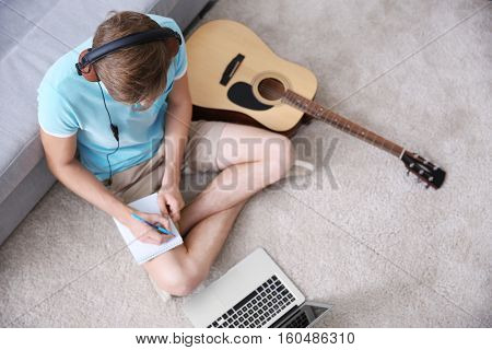 Young man composing the song and sitting on a floor