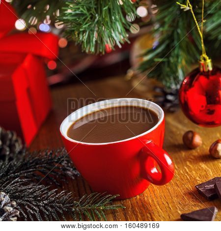 Cocoa drink in a cup near gift boxes under Christmas tree. Mug of traditional tasty winter beverage.