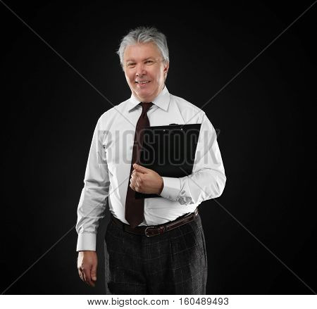 Senior businessman with clipboard on black background