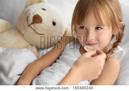 Small sick girl taking medicine